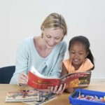 Teacher helping young girl read
